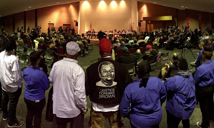 Mike Brown Sr., center, listens to part of the public comment portion of the Ferguson city council meeting in Ferguson on Tuesday, Feb. 9, 2016, where the consent decree with the United States Department of Justice was being talked about. The Ferguson city council voted to approve a modified version of the consent decree. This picture was shot as a panorama on an iPhone.  (David Carson/St. Louis Post-Dispatch via AP)