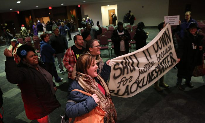 Protesters chant and yell after the Ferguson, Mo., city council meeting in Ferguson on Feb. 9, 2016, where the council voted to approve a modified consent decree with the United States Department of Justice. It is unclear if the Department of Justice will agree to the modifications. (David Carson/St. Louis Post-Dispatch via AP)