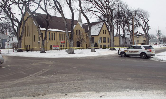 Authorities block off an area in front of Plymouth Congregational Church and near a house in north Fargo, N.D., Thursday, Feb. 11, 2016, where a suspect fired at police officers during an 11-hour standoff that left a Fargo police officer near death. Police chief Dave Todd says that Officer Jason Moszer will not survive his wounds. The suspect, who has not been identified was found dead from a shotgun wound. (AP Photo/Dave Kolpack)