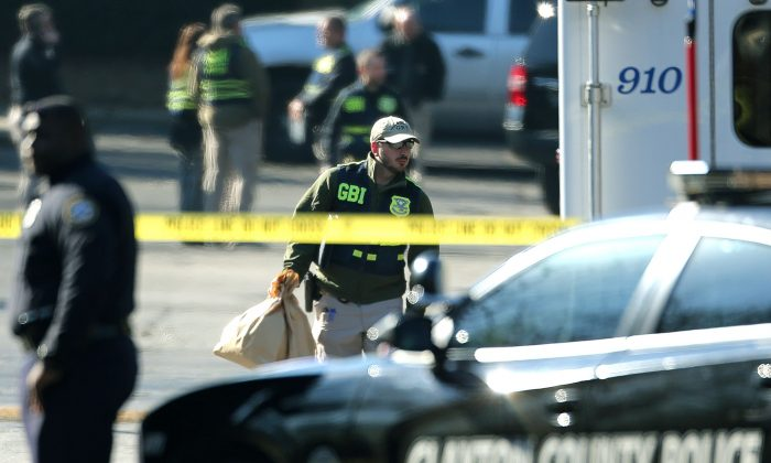 A Georgia Bureau of Investigations officer carries evidence Thursday, Feb. 11, 2016, from the scene of a fatal police shooting at the Villages on the River apartment complex in Riverdale, Ga. (John Spink/Atlanta Journal-Constitution via AP)  MARIETTA DAILY OUT; GWINNETT DAILY POST OUT; LOCAL TELEVISION OUT; WXIA-TV OUT; WGCL-TV OUT; MANDATORY CREDIT