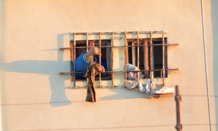 An inmate shouts and makes a hand sign from behind his barred window at the Topo Chico prison, after a riot broke out around midnight in Monterrey, Mexico, Thursday, Feb. 11, 2016. Dozens of inmates were killed and several injured in a brutal fight between two rival factions at the prison in northern Mexico, according to the state governor. (AP Photo/Emilio Vazquez)