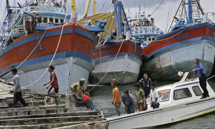Burmese fishermen arrive at the compound of Pusaka Benjina Resources to report themselves for departure to leave the fishing company in Benjina, Aru Islands, Indonesia, on April 3, 2015. (AP Photo/Dita Alangkara)
