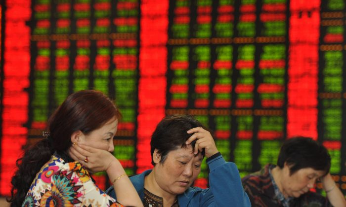 Investors check share prices in a stock firm in Fuyang, Anhui Province, east China. (AFP)