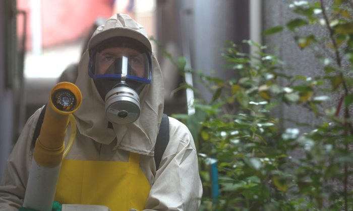 Agents working in pesticide fogging to combat the larvae of Aedes aegypti, the mosquito transmitor of the Zika virus, in the Butanta neighborhood in Sao Paulo, Brazil, on Jan. 29, 2016. (Victor Moriyama/Getty Images)
