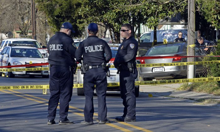 Officers investigate the scene of a shooting in Baton Rouge, La., Saturday, Feb. 13, 2016. Police officers who were shot early Saturday during a confrontation with a suspect were responding to a call about someone damaging property. (AP Photo/Bill Feig)