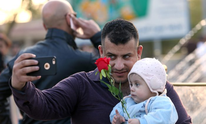 In this Saturday, Feb. 13, 2016 photo, an Iraqi man takes a photo with his child ahead of Valentine's Day at Zawra Park in Baghdad, Iraq. Baghdad is plastered with Valentine hearts and roses, and Iraqis are enjoying a rare lull in violence but wondering how long it will last. Despite recent setbacks, the Islamic State group is still dug in west of Baghdad, and increasingly powerful Shiite militias patrol the streets. (AP Photo/Hadi Mizban)