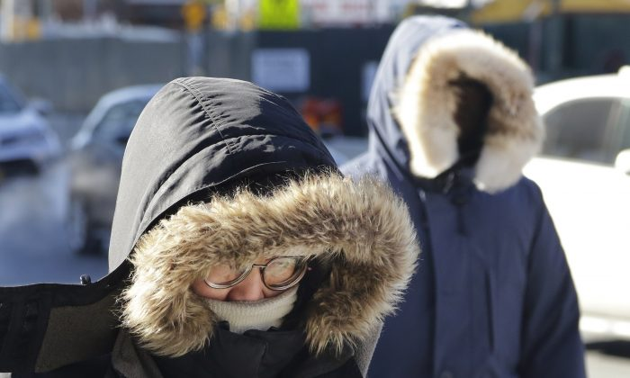 People are bundled up as they walk in cold weather, on Feb. 14, 2016, in the Queens borough of New York. Bitter temperatures and biting winds had much of the northeastern United States bundling up this weekend. (AP Photo/Mark Lennihan)