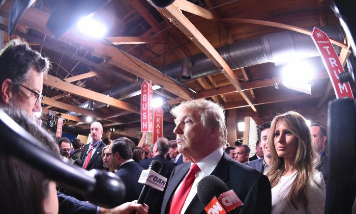 Republican presidential candidate, businessman Donald Trump, with his wife Melania Trump at right, speaks to the media after the CBS News Republican presidential debate at the Peace Center in Greenville, S.C., on Feb. 13, 2016. (AP Photo/Rainier Ehrhardt)