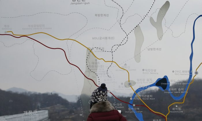 A visitor watches the North side through the glass showing a map of the Kaesong iIndustrial Complex and the border area between North and South Koreas at the Imjingak Pavilion near the border village of Panmunjom, which has separated the two Koreas since the Korean War, in Paju, South Korea, on Feb. 14, 2016. (AP Photo/Lee Jin-man)