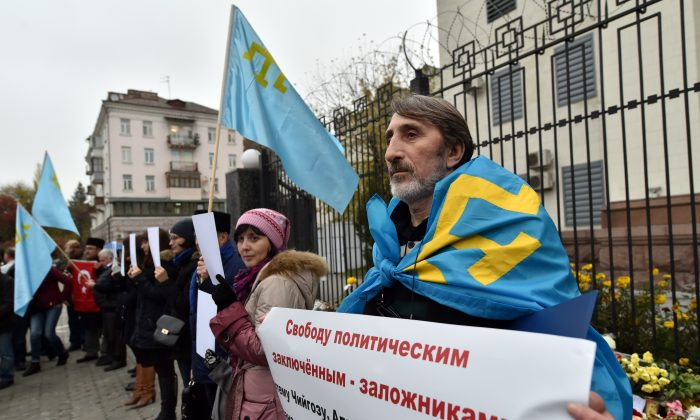 "A Crimean Tatar covered with the flag of the Crimean Tatars, holds a placard reading ""Free political prisoners-hostages"".    (SERGEI SUPINSKY/AFP/Getty Images)"