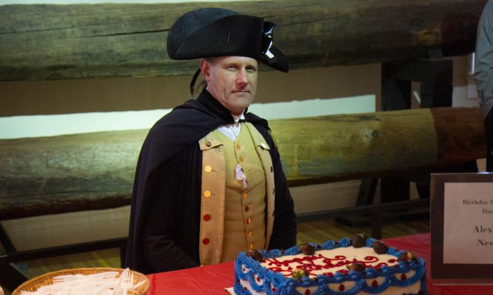 John Koopman III dressed as George Washington poses in front of a cake for George Washington's 284th birthday at his Newburgh headquarters on Feb. 13, 2016. (Holly Kellum/Epoch Times)