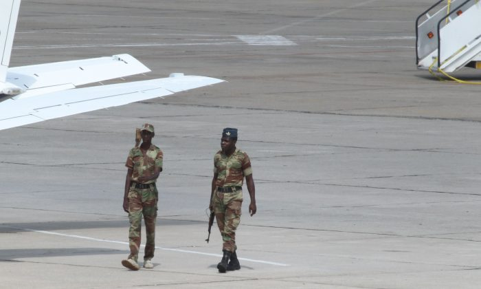 Zimbabwean Armed Soldiers patrol around a United States registered cargo plane at Harare International Airport in Harare, Zimbabwe, Monday, Feb,15.2016. Zimbabwean aviation authorities impounded a U.S.-registered cargo jet after a dead body later believed to be a stowaway and millions of South African rand were found on board, a senior official said Monday. (AP Photo/Tsvangirayi Mukwazhi)