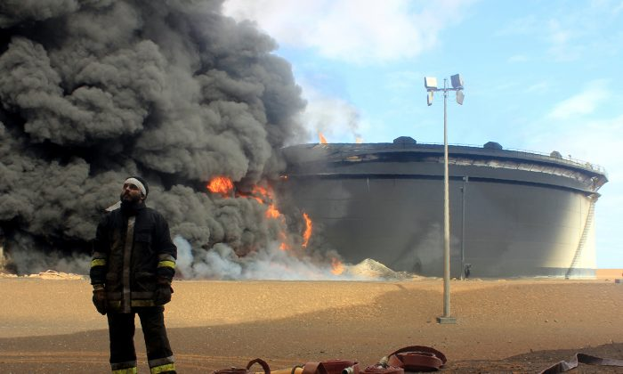 A Libyan fireman stands in front of smoke and flames rising from an oil storage tank at an oil facility in northern Libya's Ras Lanouf region on Jan. 23, 2016, after it was set ablaze earlier in the week following attacks launched by Islamic State (ISIS) jihadists to seize key port terminals. (Stringer/AFP/Getty Images)
