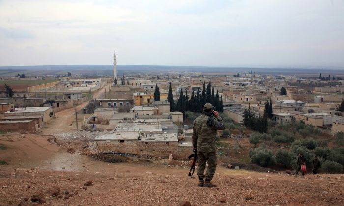A member of the Syrian government forces talks on the phone as he patrols after they took control of the village of Kiffin, on the northern outskirts of the embattled city of Aleppo, on the road leading to Gaziantep, from opposition forces on Feb. 11, 2016. (George Ourfalian/AFP/Getty Images)