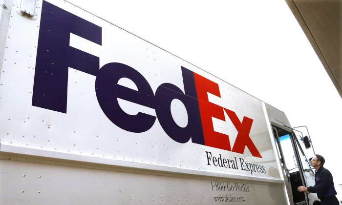 A Federal Express delivery truck driver returns to his truck after delivering a package to a business, in Springfield, Ill., on Dec. 18, 2014. (AP /Seth Perlman)