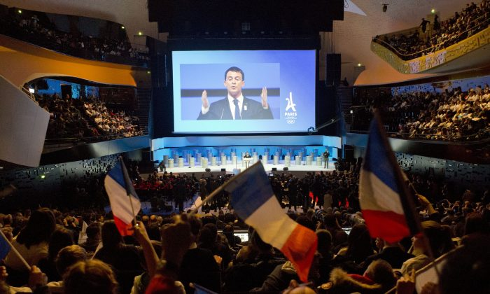 French Prime Minister Manuel Valls, projected on a giant screen, delivers his speech during the official presentation of Paris as candidate for the 2024 Olympic summer games in Paris, France, on Feb. 17, 2016. Paris, which hosted the Olympics in 1900 and 1924, is competing against Budapest, Rome and Los Angeles for the games. The International Olympic Committee will choose the host city in September 2017. (AP Photo/Francois Mori)