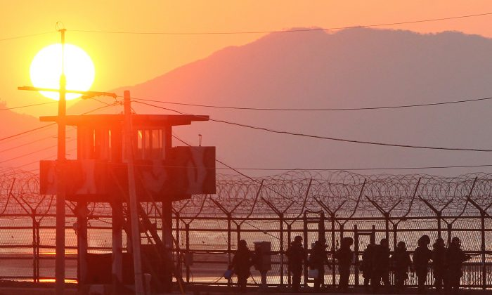 South Korean soldiers patrol along iron fence in Paju near the Demilitarized Zone (DMZ) dividing the two Koreas on Dec. 19, 2011. (Yonhap/AFP/Getty Images)