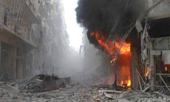 Debris cover a street and flames rise from a building following a reported airstrike by Syrian government forces on March 7, 2014, during the Friday prayer in the Sukkari neighborhood of the northern city of Aleppo. More than 250,000 people have been killed in Syria since the start of a March 2011 uprising against the Assad family's 40-year rule. (Baraa al-Halabi/AFP/Getty Images)