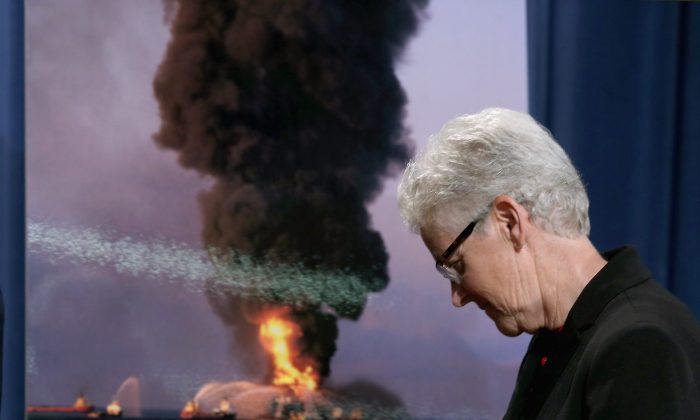 U.S. Environmental Protection Agency Director Gina McCarthy walks past a photograph of the April 2010 Deepwarter Horizon platform in flames after announcing  the resolution of federal and state claims against BP at the Robert F. Kennedy building October 5, 2015 in Washington, DC. (Chip Somodevilla/Getty Images)