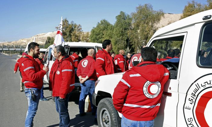 Staff from the Syrian Arab Red Crescent get ready to accompany a convoy of humanitarian aid as it waits in front of the United Nations Relief and Works Agency (UNRWA) offices before making their way into the government besieged rebel-held towns of Madaya, al-Zabadani and al-Moadhamiya in the Damascus countryside, as part of a U.N.-sponsored aid operation, in Damascus, Syria, Wednesday,  Feb. 17,  2016.  (AP Photo)