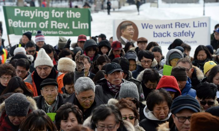 Members of Rev. Lim's congregation pray on Parliament Hill in Ottawa on Wednesday, Feb. 17, 2016, as they call for the release of Canadian Reverend Hyeon Soo Lim from his imprisonment in North Korea. (The Canadian Press/Sean Kilpatrick)