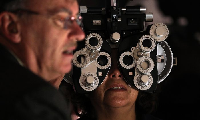 A volunteer optometrist performs a free eye exam during the Remote Area Medical (RAM) free clinic at the O.co Coliseum in Oakland, Calif., on March 22, 2012. (Justin Sullivan/Getty Images)