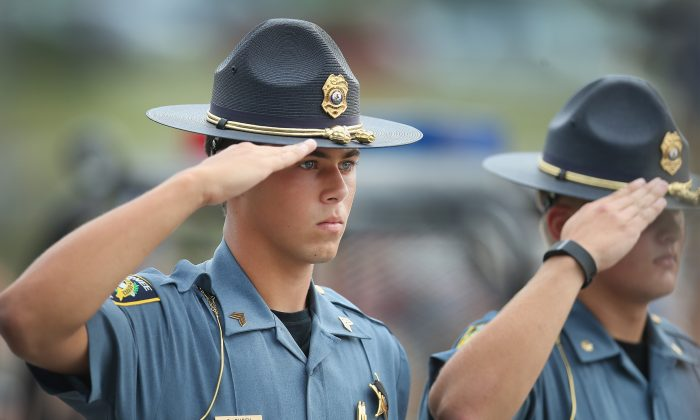 Officers salute as the family of slain Fox Lake police officer Lt. Joe Gliniewicz arrive for a vigil held in his honor in Fox Lake, Ill., on Sept. 2, 2015. Gliniewicz was shot and killed during a foot chase with three suspects. (Scott Olson/Getty Images)