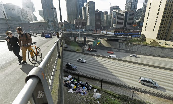 Pedestrians walk above signs of a homeless encampment near a bridge over the Interstate 5 freeway in downtown Seattle on Tuesday, Feb. 9, 2016. (AP Photo/Ted S. Warren)
