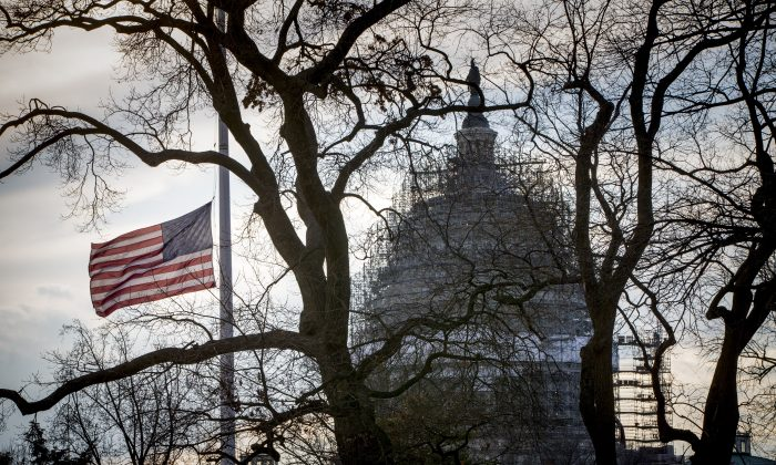 With the Capitol in the distance, the American flag flies at half-staff at the Supreme Court Wednesday, Feb. 17, 2016, in honor of Justice Antonin Scalia, who died last Saturday at age 79.  (AP Photo/J. Scott Applewhite)