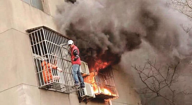 Zhang Yang forces anti-theft grating open to save woman from fire on Feb. 14, 2016. (Peng Pai)
