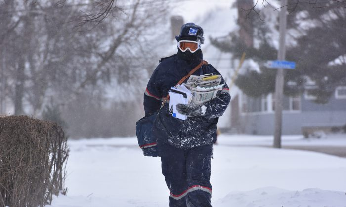 Jake Cote, a carrier with the United States Postal Service, delivers mail along Sunset Avenue, Thursday, Feb. 11, 2016, in Utica, N.Y.  (Mark DiOrio/Observer-Dispatch via AP)