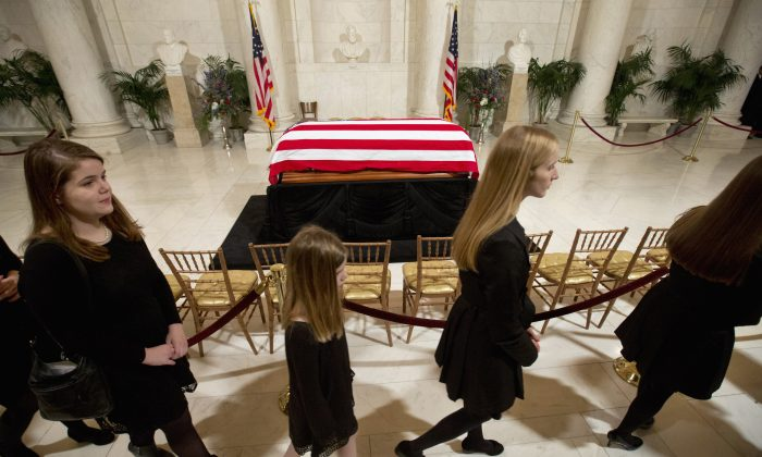 Relatives pass the casket of Supreme Court Justice Antonin Scalia as they leave a private ceremony in the Great Hall of the Supreme Court in Washington, Friday, Feb. 19, 2016, where Scalia lies in repose. (AP Photo/Jacquelyn Martin, Pool)