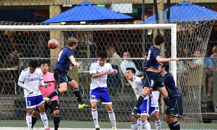 HKFC's Robbie Bacon (blue 9) has a header cleared by the Easyknit Property defence during HKFC's 4-1 victory in the division 1 of the HKFA League, at Sports Road on Sunday Feb 14. (Bill Cox/Epoch Times)