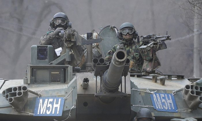 South Korean army soldiers ride a K-1 tank during the annual exercise in Paju, near the border with North Korea, on Feb. 19, 2016. (AP Photo/Ahn Young-joon)