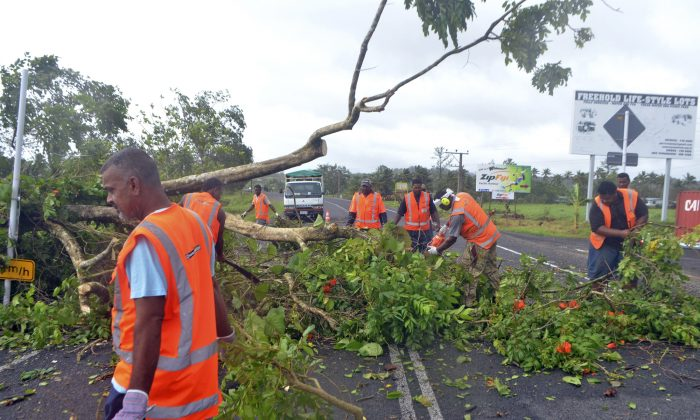 Road workers remove a fallen tree blocking a road near Lami, Fiji, Sunday, Feb. 21, 2016, after cyclone Winston ripped through the country. (Jonacani Lalakobau/Fiji Times via AP)