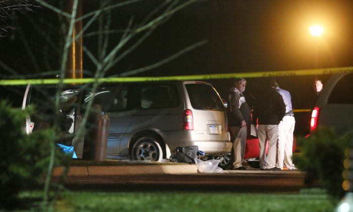 Police investigate the scene early Sunday, Feb. 21, 2016, where people were shot in vehicles outside a Cracker Barrel restaurant in Kalamazoo, Mich. A man drove around Kalamazoo shooting people at three locations Saturday, leaving six dead and three injured, two of them critically, police said. Police have arrested the suspect in the Saturday, Feb. 20, multiple shootings. (Mark Bugnaski/Kalamazoo Gazette)