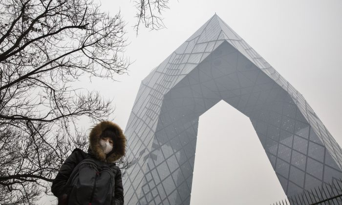 A Chinese woman wears a mask to protect against pollution as she passes the CCTV building in heavy smog on Dec. 8, 2015 in Beijing, China. (Kevin Frayer/Getty Images)