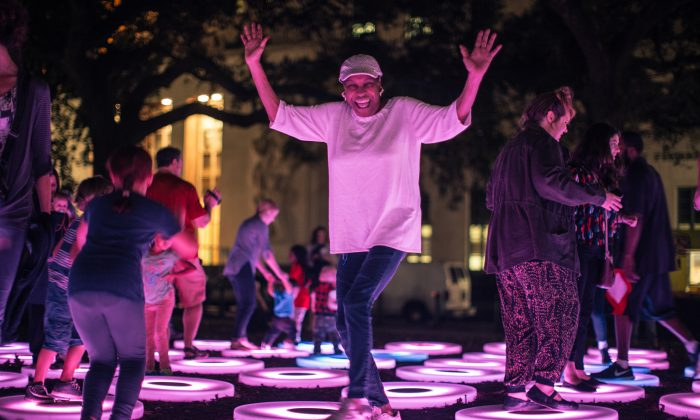 "This Dec. 3, 2015 photo provided by Arts Council New Orleans shows people interacting with ""The Pool,"" a work that was part of New Orleans' LUNA Fete light festival. (Marcus Carter/Arts Council New Orleans via AP)"