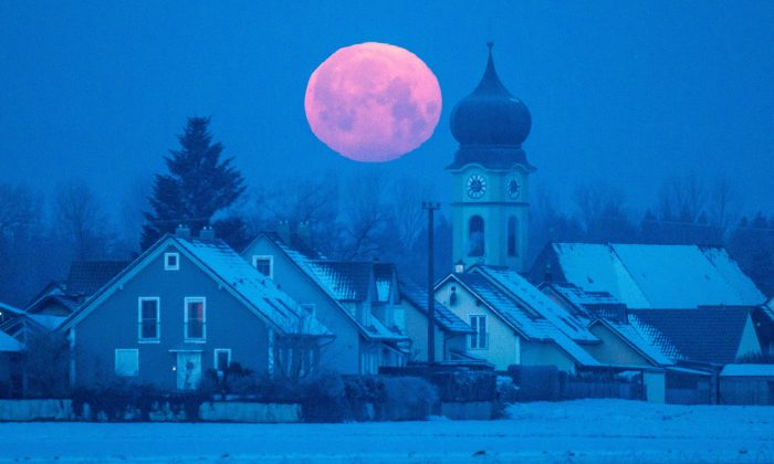 Full moon sets behind the parish church of Schoenach near Regensburg, southern Germany, on February 4, 2015. (Armin Weigel/AFP/Getty Images)