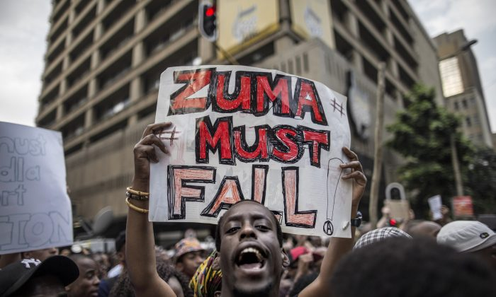 """A student holds a placard reading """"Zuma must fall"""" outside the Luthuli House, the African National Congress (ANC) party headquarters, on Oct. 22, 2015, in Johannesburg, during a demonstration of thousands of students against university fee hikes, government corruption, and economic turmoil. (Marco Longari/AFP/Getty Images)"""