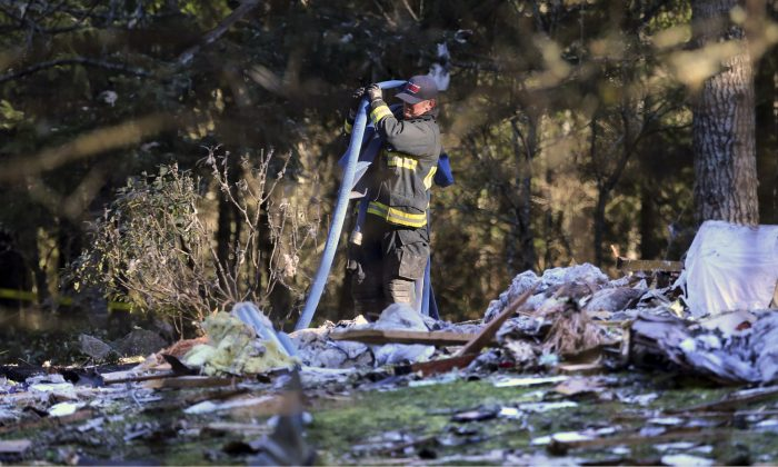 A South Kitsap Fire and Rescue firefighter collects a hose at the site of a home explosion in the 3800 block of Soholt Lane SE in Port Orchard, Wash. on Tuesday, Feb. 23, 2016. The remains of two people were found following a powerful explosion Tuesday morning that leveled a home in Western Washington. (Larry Steagall/Kitsap Sun via AP)