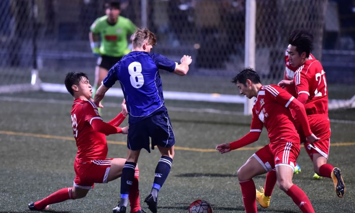 Frederick Schipper is stopped by the Wanchai defence during their 1-nil victory in the HKFA first division match at Sports Road on Saturday Feb 20, 2016. (Bill Cox/Epoch Times)