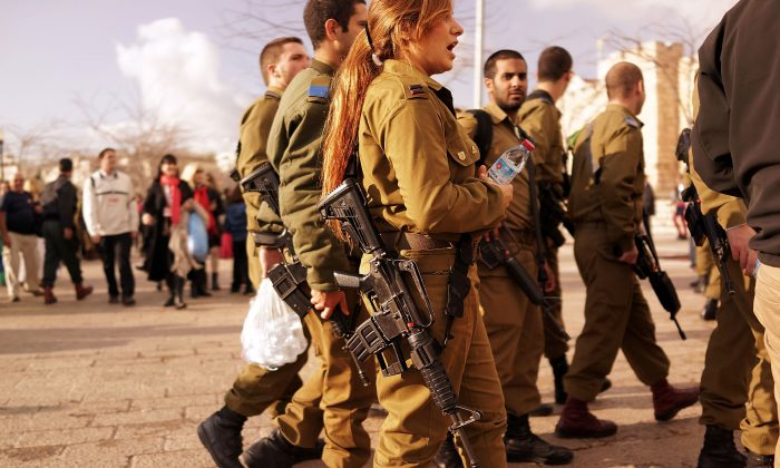 Young members of the Israeli Defense Forces (IDF) pause in a park near the Old City on Nov. 28, 2014, in Jerusalem, Israel. Soldiers with the IDF are now required to carry their firearms while off duty. (Spencer Platt/Getty Images)