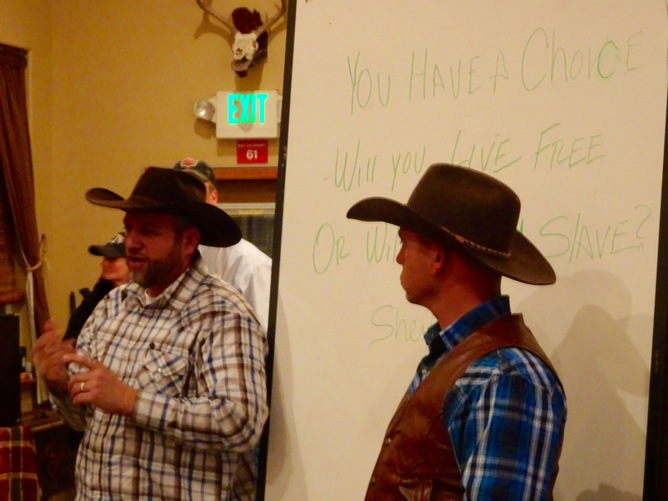"""Occupiers Ammon and Ryan Bundy ask Harney County Ranchers whether they will """"live free or be a slave?"""" just before imploring Harney County ranchers to break their BLM grazing leases, in Crane, Ore., on Jan. 18. (Peter Walker)"""