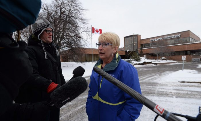 Debbie Cole, president of the Ottawa Newspaper Guild, speaks to reporters outside the offices of the Ottawa Citizen and Ottawa Sun on Jan 19 after Postmedia announced it was cutting approximately 90 jobs and merging newsrooms in four cities in an effort to slash costs amid mounting revenue losses. (THE CANADIAN PRESS/Sean Kilpatrick)