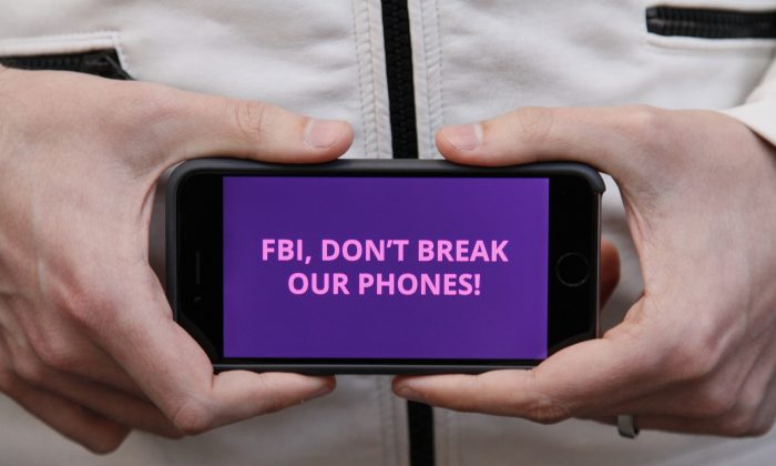 A man holds out his iPhone during a rally in support of data privacy outside the Apple store in San Francisco on Feb. 23, 2016. Protesters assembled in more than 30 cities to lash out at the FBI for obtaining a court order that requires Apple to make it easier to unlock an encrypted iPhone used by a gunman in December's mass murders in California. (AP Photo/Eric Risberg)
