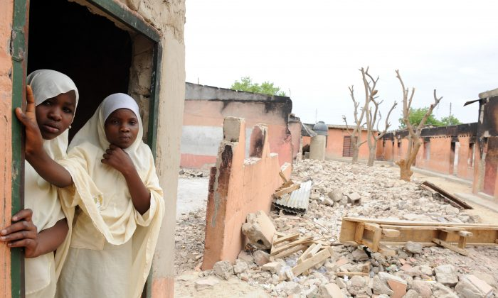A female student stands in a burnt classroom at Maiduguri Experimental School, a private nursery, primary, and secondary school burnt by the Islamic terrorist group Boko Haram to keep children away from school in Maiduguri, northeastern Nigeria, on May 12, 2012. (Pius Utomi Ekpei/AFP/GettyImages)