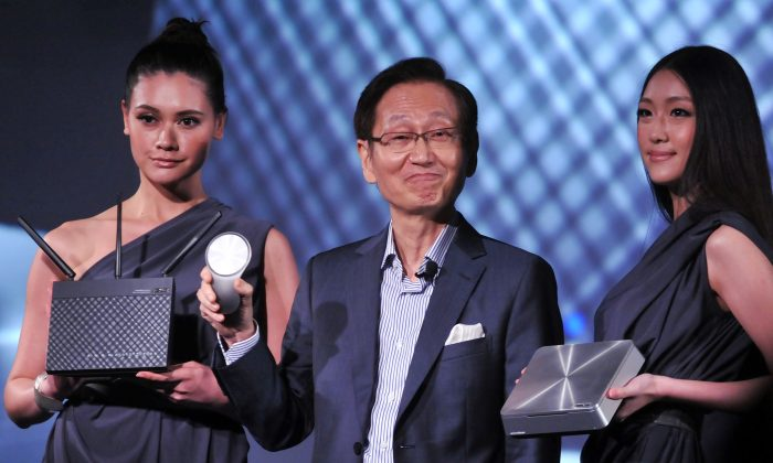 Jonney Shih (C), Chairman of Taiwan's ASUSTek Computer Inc., showcases a router during a press conference in Taipei, Taiwan, on June 3, 2013. ASUS is now required to put new security standards in place, after it was found its routers exposed user data. (Mandy Cheng/AFP/Getty Images)