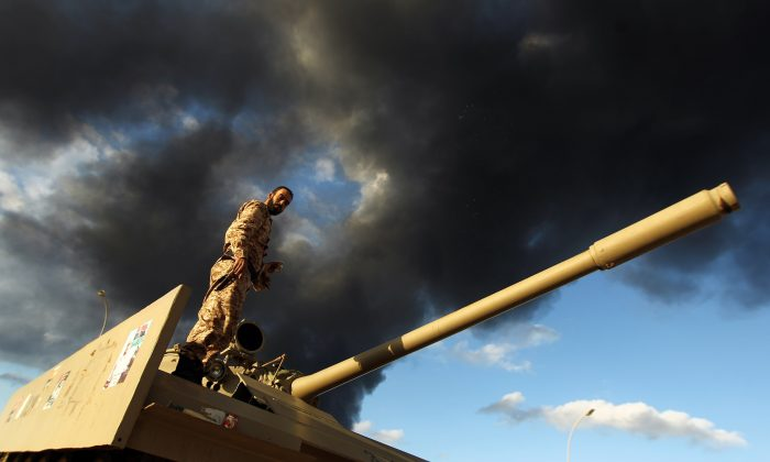 A Libyan army soldier stands on a tank as heavy black smoke rises from the city's port in the background after a fire broke out at a car tyre disposal plant during clashes against Islamist gunmen in the eastern Libyan city of Benghazi on Dec. 23, 2014. (Abdullah Doma/AFP/Getty Images)