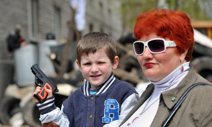 A boy with his mother holds a toy pistol at a barricade outside the police regional building seized by the separatists in the eastern Ukrainian city of Slavyansk on April 17, 2014. (GENYA SAVILOV/AFP/Getty Images)